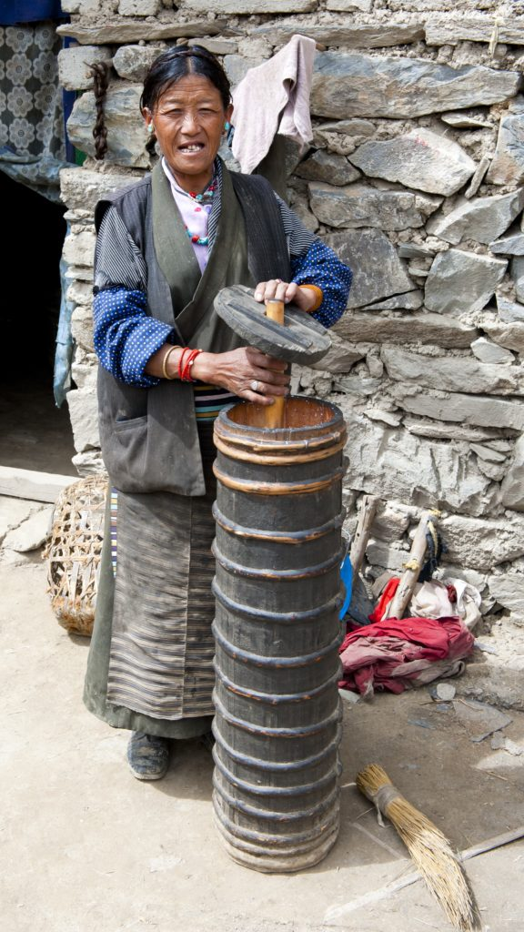 Tibetan woman making Yak Butter Tea.